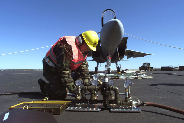 US Air Force Technical Sergeant Donnie Stricklan, 1ST Equipment Maintenance Squadron, connects a hose from an air compressor to inflatable tarps during an aircraft lift scenario for the 1ST Fighter Wing's March 2001 Operational Readiness Inspection at Langley Air Force Base, Virginia. (Duplicate image, see also DFSD0201626 or search 010319F3405C008)