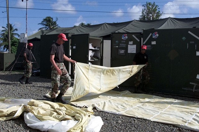 US Air Force Airmen of the 820th RED HORSE Squadron, Nellis Air Force Base, Nevada fold a portable tent covering as they prepare for redeployment back to the United States, as the completion of Exercise NEW HORIZONS 2001 in St. Lucia comes to a completion. The Exercise provided much needed humanitarian assistance to impoverished nations throughout South and Central America, while providing unique and valuable training to active duty and reserve components of the US Military