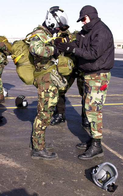 Combat controller jump master US Air Force STAFF Sergeant Monty Koose performs a jump master's inspection on US Air Force SENIOR AIRMAN Matthew Bower, both of the 22nd Special Tactics Squadron, McChord Air Force Base, Washington, before boarding an Air National Guard C-130 Hercules aircraft (not shown) for a jump during Exercise NORTHERN EDGE 2001