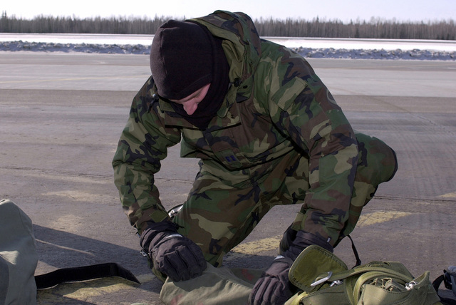 Combat controller, US Air Force Captain Wallpert from the 22nd Special Tactics Squadron, McChord Air Force Base, Washington, gears up for a jump master inspection before boarding an Air National Guard C-130 Hercules aircraft (not shown) for a jump involving a snowmobile insertion during Exercise NORTHERN EDGE 2001