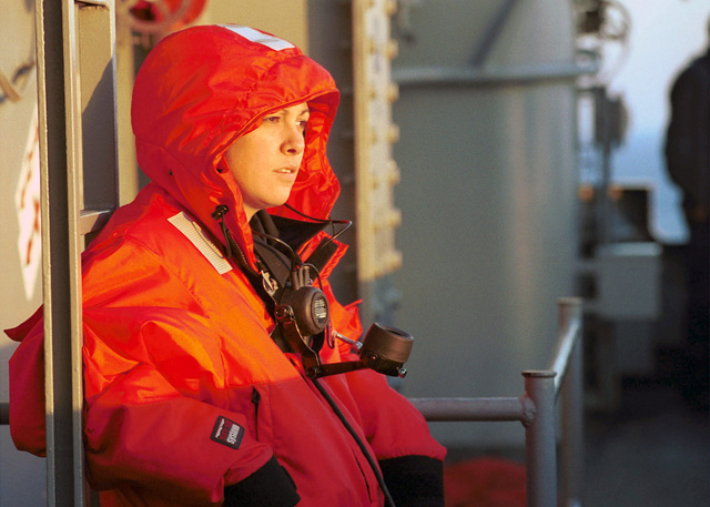 Operations SPECIALIST Third Class Andrea Ramirez stands watch on the signal bridge of USS Harry S. Truman (CVN 75) during an underway replenishment with US Naval Ships (USNS) Concord (T-AFS 5) and USNS Pecos (T-AO 197). Signal bridge watches during sunrise are breath taking as the sun gives birth to a new day in the Arabian sky; non the less, watchstanders play a crucial role in keeping the ship away from other ships that may be less detectable by radar compared to the human eye. TRUMAN is on station in the Arabian Gulf in support of Operation SOUTHERN WATCH. SOUTHERN WATCH establishes a southern no fly zone over Iraq and extends to the borders to just south of Baghdad, capital city of Iraq