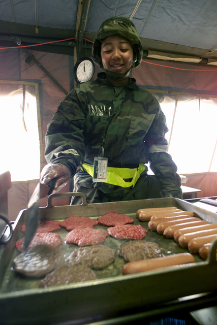 US Air Force AIRMAN First Class Kimberly Shannon a Food Service Specialists with the 1ST Services Squadron, Langley AFB Virginia prepare hamburgers and hotdogs for lunch, inside the deployed dining facility, during the 1ST Fighter Wing's Operational Readiness Inspection. (Duplicate image, see also DFSD0203483 or search 010321F5718M021)