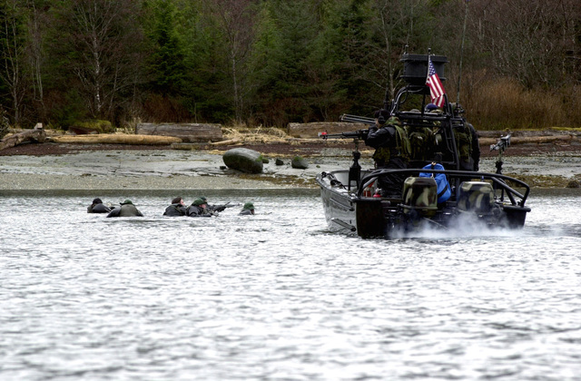 Members of Navy Seal Team 5, San Diego, California, swim to shore as members from Navy Special Boat Unit 22, Sacramento, California, provides cover for them during an incursion exercise during NORTHERN EDGE 2001, in Alaska
