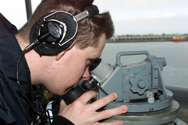 Quartermaster SEAMAN Collin Corbin, USS Anchorage LSD-36, shoots bearings while pulling out of Port at 32nd Street San Diego, California, during Exercise KERNEL BLITZ 2001