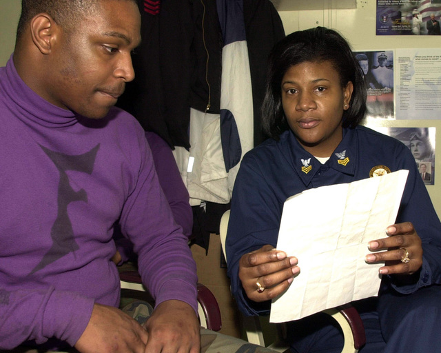 Navy Career Counseler 1ST Class Ebony Henry discusses the benefits of striking (entering a new job specialty) to Aviation Boatswain's Mate Fuels AIRMAN Donald Woolridge during Exercise KERNEL BLITZ 2001. KERNEL BLITZ is a large-scale amphibious landing exercise taking place in the vicinity of Camp Pendleton, Calif. Approximately 25 ships, 75 aircraft and 15,000 Sailor, Marines, solders, airman and Coast Guardsmen representing four nations are participating in the exercise