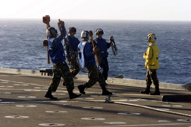 The flight deck crew of the USS Anchorage (LSD-36) gets within sight of the helicopter pilot for visual confirmation that chocks and chains are removed before take off during Exercise KERNEL BLITZ 2001. KERNEL BLITZ is a large-scale amphibious landing exercise taking place in the vicinity of Camp Pendleton, California. Approximately 25 ships, 75 aircraft and 15,000 Sailor, Marines, solders, airman and Coast Guardsmen representing four nations are participating in the exercise