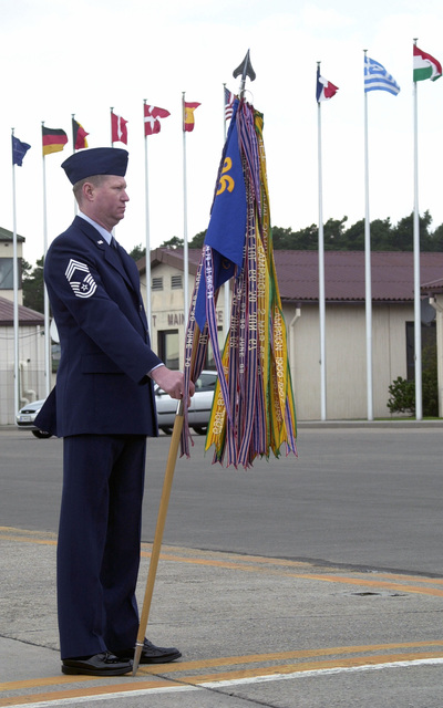 CHIEF MASTER Sergeant (CMSGT) William Hendley guidon bearer 86TH Communication Group, Ramstein Air Base, Germany stands at parade rest during the 86th Airlift Wings Retreat Ceremony at Ramstein Air Base, Germany on 30 March 2001