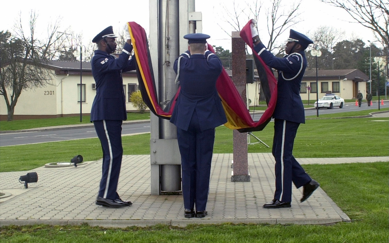 SENIOR AIRMAN (SRA) David Sands, AIRMAN First Class (A1C), Andrew Absher and A1C Jonathan Richardson all members of the 86th Airlift Wings Honor Guard fold the German flag during the Wing Retreat Ceremony at Ramstein Air Base, Germany on 30 March 2001