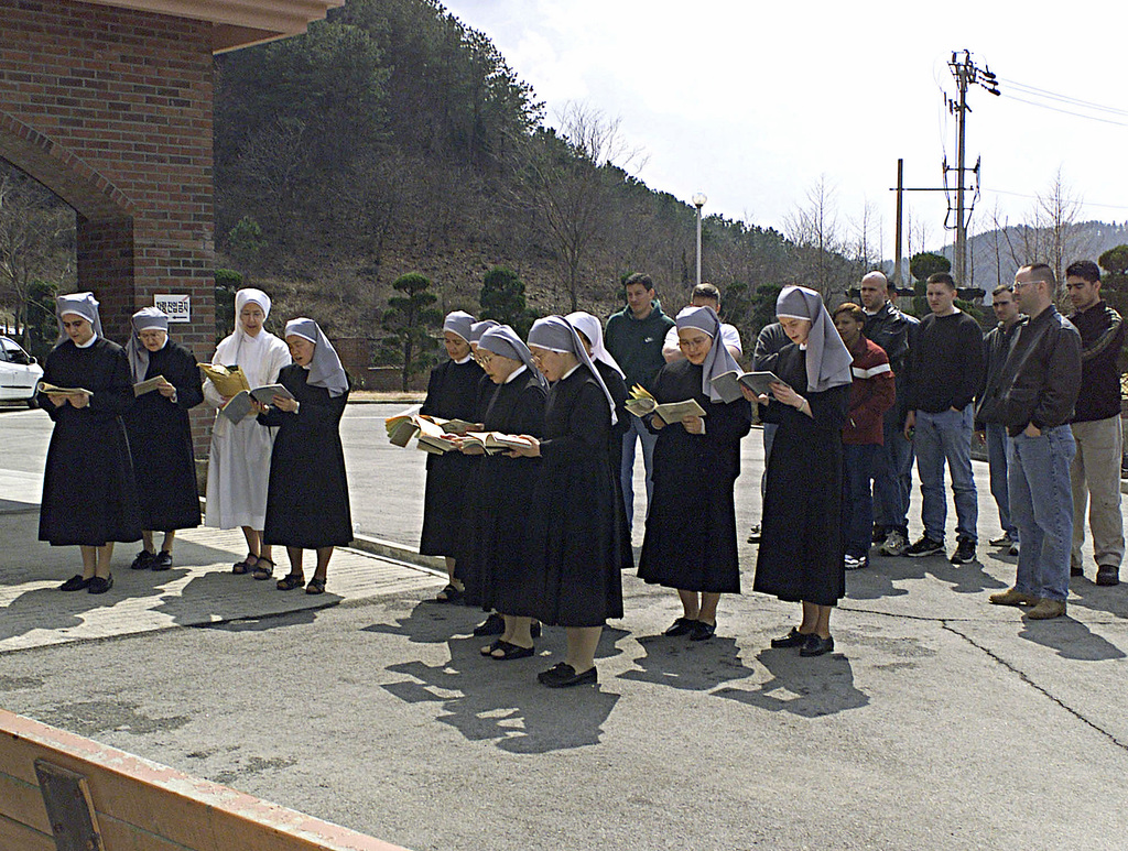 """Community service helps keep good relations with military members and the Korean community. Marine volunteers from HMLA-267 and the Air Force join in with the """"Little Sisters of the Poor"""" during their afternoon prayer. Then proceed with washing windows, picking up trash, and getting to know some of the residents at the Mount St. Joseph Home for the Aged during MILLENNIUM EDGE in Chonju, Korea. MILLENNIUM EDGE is a joint and combined training exercise conducted in the Republic of Korea with assets from Marine and Air Force units. The exercise gives both the pilots and ground crew members a chance to operate in an unfamiliar place with different types equipment"""