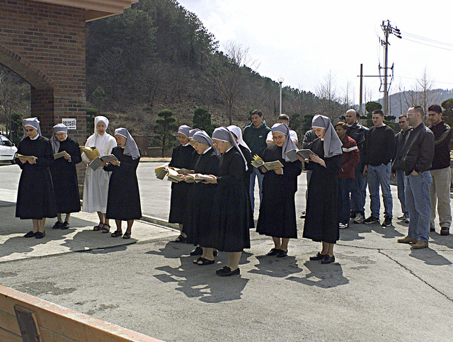 "Community service helps keep good relations with military members and the Korean community. Marine volunteers from HMLA-267 and the Air Force join in with the ""Little Sisters of the Poor"" during their afternoon prayer. Then proceed with washing windows, picking up trash, and getting to know some of the residents at the Mount St. Joseph Home for the Aged during MILLENNIUM EDGE in Chonju, Korea. MILLENNIUM EDGE is a joint and combined training exercise conducted in the Republic of Korea with assets from Marine and Air Force units. The exercise gives both the pilots and ground crew members a chance to operate in an unfamiliar place with different types equipment"