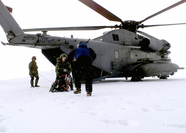 A crewmember assigned to the 352nd Special Operations Group (SOG), Royal Air Force (RAF) Mildenhall, UK assist an investigation team member to offload equipment from a USAF MH-53 PAVE LOW helicopter in the Scottish Highlands. The 352ND SOG is assisting in the search for two downed F-15C Eagle aircraft from the 493rd Tactical Fighter Squadron. The aircraft were reported missing after losing contact in the Scotland Highlands