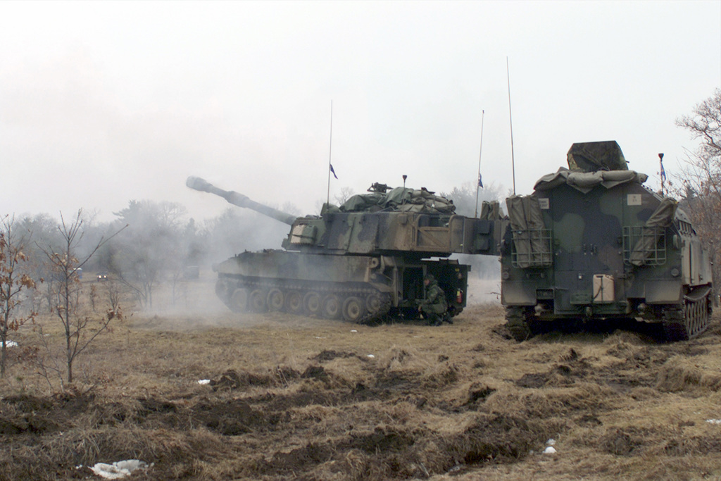 """A US Army M109A6 155mm """"Paladin"""" self-propelled howitzer fires its main gun down range at the Multiple Purpose Training Range (MPTR) at Fort McCoy, Wisconsin. An M992 Field Artillery Ammunition Support Vehicle (FAASV) is parked in support position"""