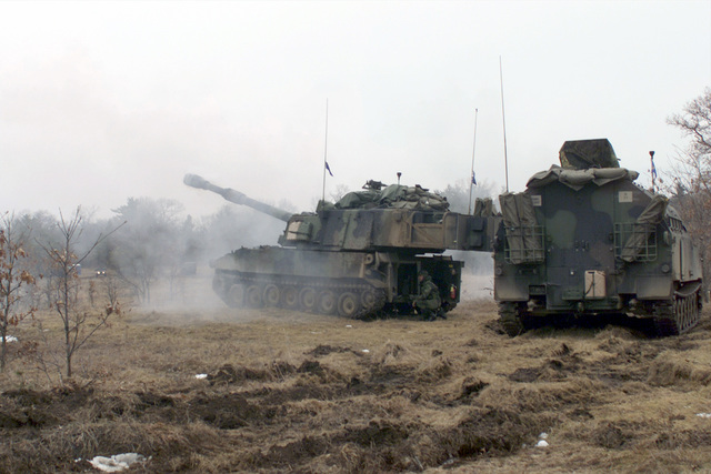 "A US Army M109A6 155mm ""Paladin"" self-propelled howitzer fires its main gun down range at the Multiple Purpose Training Range (MPTR) at Fort McCoy, Wisconsin. An M992 Field Artillery Ammunition Support Vehicle (FAASV) is parked in support position"