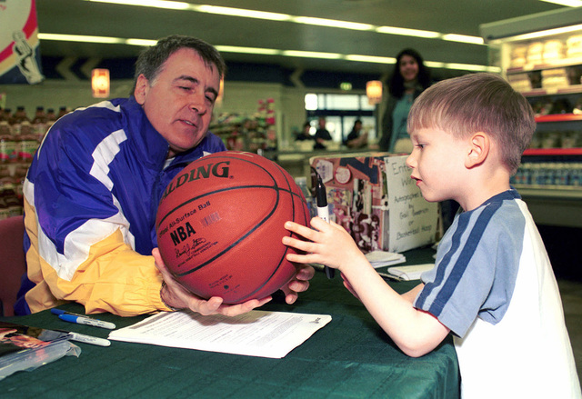 Ryan Caron, a five-year old dependant at Royal Air Force (RAF), Lakenheath, UK gets National Basketball Association (NBA) Hall-of-Famer Gail Goodrich to autograph his basketball. Mr. Goodrich is part of the 3RD Annual Hardcourt Hero's European Tour, where former NBA players are visiting 13 United States military bases throughout England and Germany