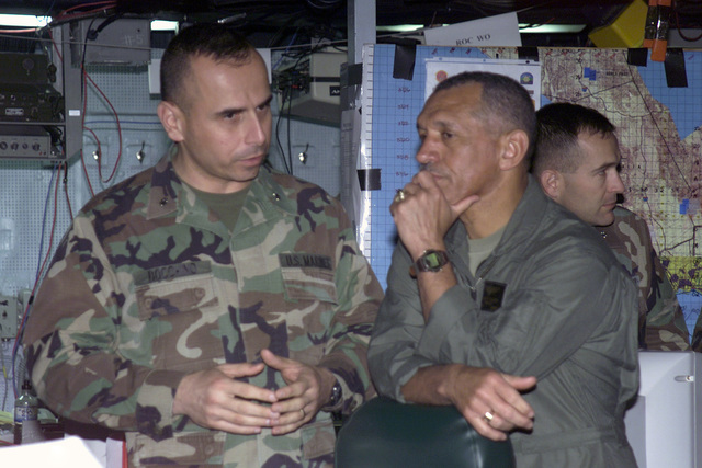 US Marine Corps (USMC) Major General (MGEN) Charles Bolden (foreground right) receives a briefing from USMC Lieutenant Colonel (LTC) J. J. Boccino, inside the Operations Center, onboard the USS BONHOMME RICHARD (LHD 6), during Exercise KERNEL BLITZ 2001