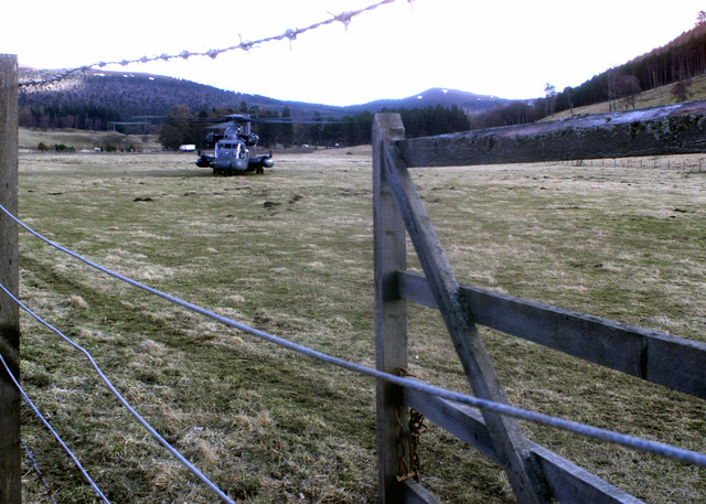 A USAF MH-53 PAVE LOW helicopter assigned to the 352ND Special Operations Group (SOG), 21ST Special Operations Squadron (SOS), Royal Air Force (RAF) Mildenhall, sits in a field in Braemar Scotland, waiting to pick up the Braemar mountain rescue team. The helicopter and crew deployed to RAF Kinloss to assist in the recovery of two USAF F-15C Eagle aircraft, that went down during a training mission over Scotland