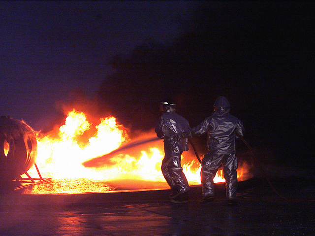 At night, members of the Marine Corps base fire department emergency rescue team, in Joint-Firefighter Integrated Response Ensemble (J-FIRE), extinguish the fire around the aircraft simulator. The United States Naval Hospital of Camp Lester, Okinawa, Japan, held a medical evacuation drill, simulating a plane crash with numerous injuries and casualties
