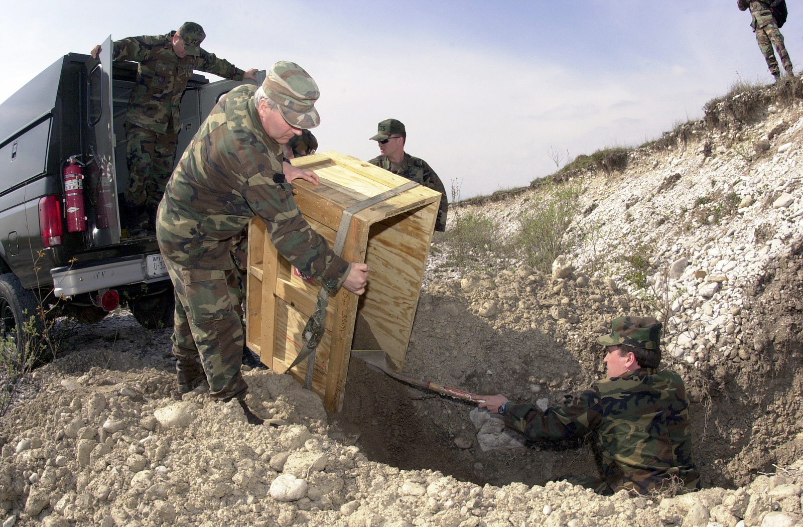 CHIEF MASTER Sergeant (CMSGT) Pepe Giacomo, and Warrant Officer Laurano Agostino, 3RD Regiment of Engineers, Udinese Army Detachment, use sand to cover unexploded ordnance at the Maniago Range, in Italy. The unexploded ordnance was uncovered by construction worker while digging trenches for waterlines during Aviano 2000 (AV2K) construction. USAF Explosive Ordnance Disposal (EOD) personnel assigned to the 31ST Civil Engineer Squadron, Aviano AB, Italy helped with the disposal project