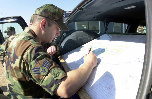 SENIOR AIRMAN (SRA), Daniel Kane, USAF, Aviano 2000 (AV2K) Program Manager assigned to the 31ST Communications Squadron, Aviano AB, Italy checks safety maps to ensure no communications line are being endangered by the discovery of unexploded ordnance found at one of the construction sites
