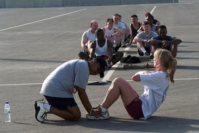 US Navy (USN) Aviation Maintenance Administrationman First Class (AZ1) Taresha Foxx assists Aviation Support Equipment Technician (AS) SENIOR CHIEF PETTY Officer (SCPO) Michelle Morgante with sit-ups during the Physical Readiness Test (PRT) while in port at Jebel Ali, United Arab Emirates (ARE) during Operation SOUTHERN WATCH