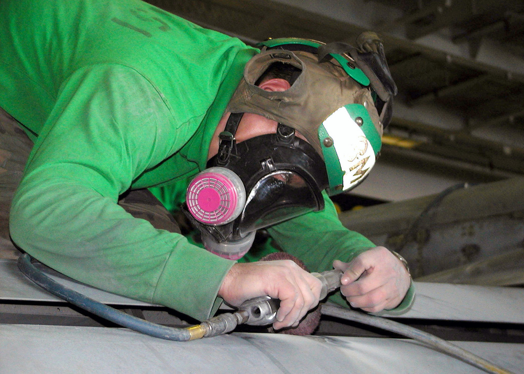 "US Navy (USN) Aviation Structural Mechanic 2nd Class (AM2) Mahler, removes corrosion from the wing of an F-14 ""Tomcat"" aircraft, in the hangar deck aboard USS Constellation (CV 64)"