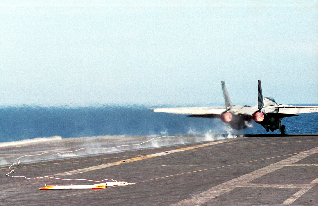 """A US Navy (USN) F-14 """"Tomcat"""" aircraft catapults from the flight deck of the USS KITTY HAWK (CV 63), with a target banner in tow"""
