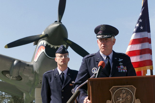 """14th Air Force Commander Major General William """"Bill"""" R. Looney III speaks of the prestige and history of the P-40E Tomahawk that stands behind him at the ceremonial unveiling, on April 17, 2001, of the replica aerial fighter. The monument is located at the headquarters of the 30th Space Wing at Vandenberg Air Force Base, California. The P-40 """"serves as, a monument, not to the aircraft but to the people of the original Flying Tigers, and as reminder to their modern-day counter-parts."""" The Warhawk memorial, funded by the 14th Air Force with Major General William R. Looney III in command, took three months from ground breaking to the dedication ceremony"""