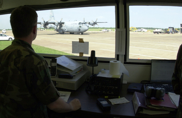US Air Force Major Pete Mastroianni from the 821st Air Mobility Squadron, McGuire Air Force Base, New Jersey, watches from the Mobility Air Reporting and Communications System (MARC) as a C-130 Hercules aircraft from Pope Air Force Base, North Carolina, taxies onto the Intermediate Staging Base ramp in Alexandria, Louisiana. Canadian Air Force aircraft and personnel from 2nd Air Movement Squadron, Trenton, Ontario, and US Air Force aircraft from the 2nd Airlift Squadron at Pope Air Force Base, North Carolina, and aerial port personnel from the 821st Air Mobility Squadron, McGuire Air Force Base, New Jersey, combined forces to provide airlift support for the US Army's 2nd Battalion, 10th ...