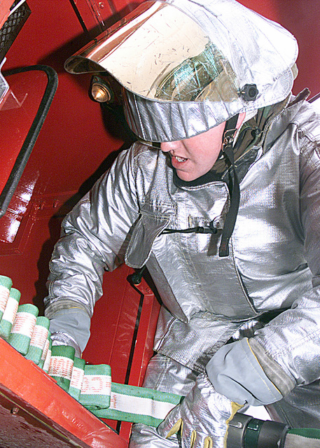 AIRMAN (AMN) Erik Waldrod, of the 92nd Civil Engineering Squadron, Fairchild Air Force Base, Washington, recoils firehoses after a simulated cockpit fire during Operational Readiness Inspection (ORI) EXERCISE CRISIS REACH 01-49. AMN Waldrod is wearing aluminized turnout gear or Crash/Fire/Rescue Suit (CFR) used by fire fighters in high heat applications