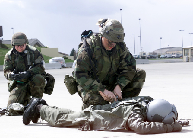 "A""downed enemy""pilot parachutes on the flightline and being detained and cuffed by Technical Sergeant (TSGT) Dan Heering, USAF, (right), 92nd Security Forces Squadron (SFS). AIRMAN First Class Tessy Buckalew, USAF, 92nd SFS begins to call the capture in to the exercise command post. The simulation occurred during the Operational Readiness Inspection (ORI) Crisis Reach 01-49, at Fairchild Air Force Base, Washington.  TSGT Heering is wearing MILES (Multiple Integrated Laser Engagement System) gear"