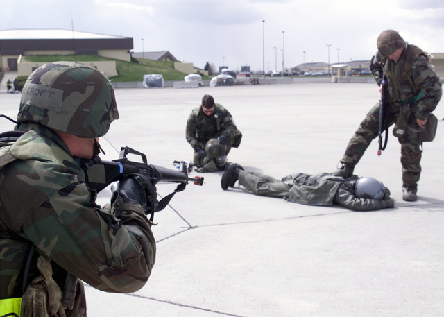 "Simulation of an""enemy""pilot parachuted in after his aircraft is shot down. He landed on the flightline where 92nd Security Forces Squadron personnel Technical Sergeant Dan Heering, USAF, (right) and AIRMAN First Class (A1C) Tessy Buckalew, USAF, (center), apprehend and secured the pilot. Augmentee A1C Michael Croft, 92nd Civil Engineering Squadron maintains cover on the prisoner with a Colt 5.56 mm M16A1 rifle. Ground personnel are in Mission-Oriented Protective Posture response level 2 (MOPP-2) gear"