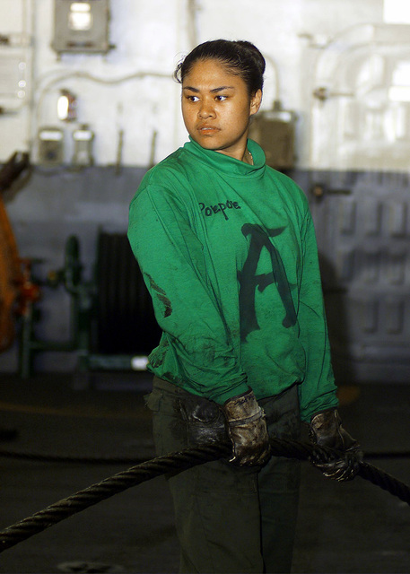US Navy AIRMAN Cassie Poepoe flanks out an arresting gear cable in the hangar bay of USS HARRY S. TRUMAN (CVN 75). Arresting cables are used on the flight deck to arrest or stop the aircraft as it lands on the flight deck. Truman is on station in the Persian Gulf in support of Operation SOUTHERN WATCH