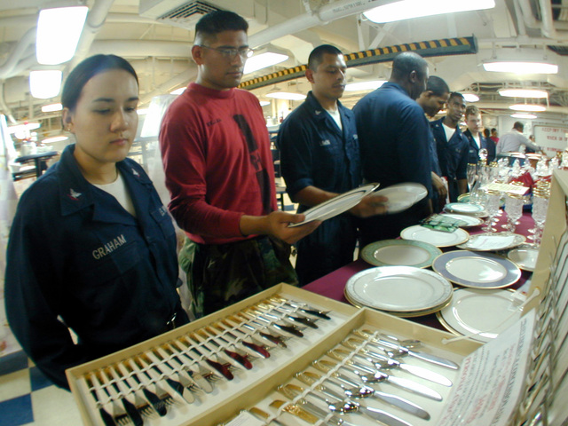 (from left to right) US Navy Mess SPECIALIST Third Class Miranda Graham, US Navy Aviation Ordnanceman Third Class Jose Vega and US Navy Aviation Ordnanceman Third Class Carlos Limon browse a vendor stand on the forward mess decks of USS HARRY S. TRUMAN (CVN 75), which is selling goods from the Navy Exchange to the crew while on deployment. (SUBSTANDARD)