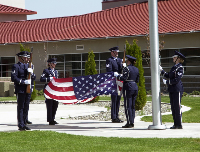 Members of the 173rd Fighter Wing, Kingsley Field Honor Guard, prepare to fold the US flag during a retreat ceremony while Command MASTER Sergeant Gene Hill tells what each fold of the flag represents
