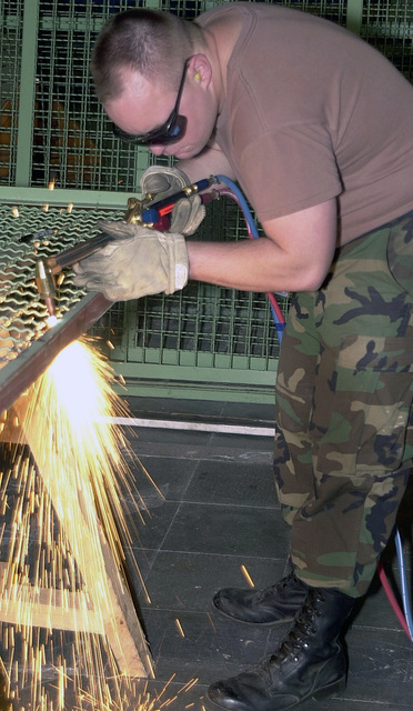 """At Istres Air Base, STAFF Sergeant (SSGT) John Douglas, USAF, cuts the frame of a metal cage door as part of a project to expand a storage area at the Air Force detachment on the French air base. SSGT Douglas deployed with three others from the 3rd Civil Engineers, Elmendorf Air Force Base, Alaska, on a 90-day Air Expeditionary Force deployment with the 16th Expeditionary Operations Group here as part of Operation JOINT FORGE. """"The United States has agreed to provide a force of approximately 6,900 U.S. Service member to help maintain a capable military force in Bosnia-Herzegovina. No timetable for the duration of Operation JOINT FORGE has been determined. The mission will be assessed..."""