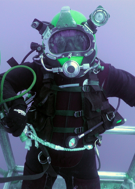 US Navy (USN) Boatswain Mate CHIEF, 1ST Class Diver/Surface Warfare, David Calloway, stand inside a divers cage as he ascends from a dive over the historical wreck of the USS Monitor, 17 miles off the coast of North Carolina, during the first phase of Monitor Expedition 2001
