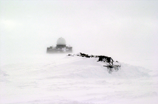 "The 109th Airlift Wing (AW) Arctic Aircraft Recovery School (aka ""Kool School"") members will recover these snow bound equipment pallets. In the background is an abandoned Early Warning Radar Site, part of the former DEW (Distant Early Warning) system. The school is located on the Ice cap of Greenland just three miles from the abandoned DYE II site"