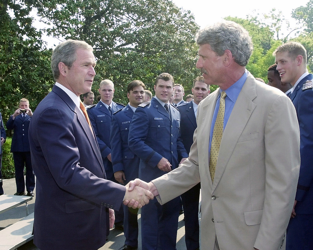 President George W. Bush congratulates Tom Miller, Special Teams Coordinator/Falcon Backs, a member of the Air Force Academy Falcon football team coaching staff, after presenting the Commander and CHIEF's Trophy to the team in a ceremony on the White House South Lawn, Washington, D.C. The trophy awarded annually to the winner of a round robin tournament between the service academies. The Air Force Academy has won the trophy 10 of the last 12 years. The senior class accepting the trophy has never lost a game to any of the other service academies