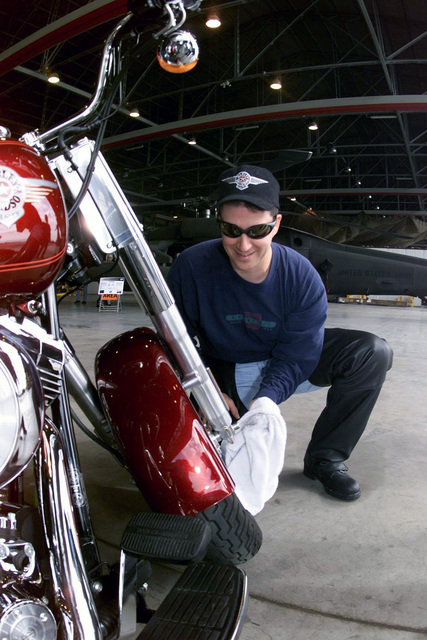 Technical Sergeant Bill Deakin, USAF, 31st Civil Engineering Squadron, electrician, wipes down his Harley-Davidson Fatboy FLSTF, preparing it for display at Aviano Air Base, Italy. He is part of the Aviano Hogs chapter, and using an Aviano family fair to promote motor cycle safety