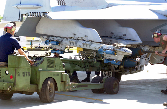 Private First Class Samual Gregorey, USMC, drives the MHU-83 C/E Munitions Loading System. Other members from the 533rd Marine Strike Fighter Squadron (VMFA) prepare to load three 305 pound Mk 81 practice bombs with Mk 15 bomb retarding fins attached, onto the F/A-18D Hornet during Exercise TANDEM THRUST. The F-18 is also carrying six BDU-48/B 10-pound practice bombs on the A/A37B-6E Multiple Ejector Rack. TANDEM THRUST is a combined US, Australian, and Canadian military training exercise. This biannual exercise is being held in the vicinity Shoalwater Bay training area, Queensland, Australia. The purpose Exercise TANDEM THRUST is to train for crisis action planning and execution...