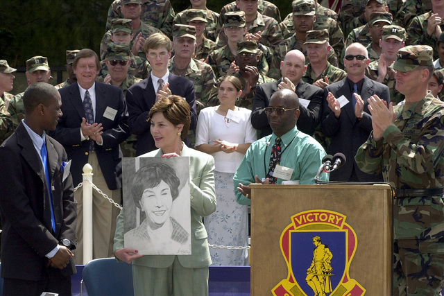 After addressing the soldiers and children at Pinckney Elementary School, Fort Jackson, South Carolina, First Lady Laura Bush accepts a pencil drawn portrait by and from Spring Valley High School Junior Tyrell Brown (left). Mr. Brown spoke to the gathering about the difference his History teacher retired Army Sergeant First Class Franklin Davis (left) made in his life. Major General Raymond Barrett, (far-left) USA, commander, Fort Jackson joins in the applause