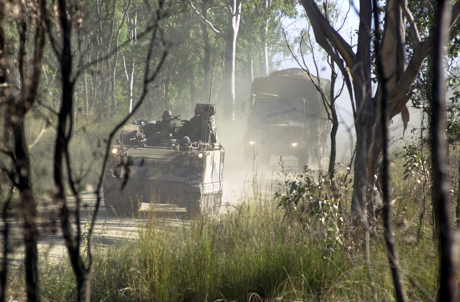 An Australian M113A1 Armored Personnel Carrier (APC) leads a convoy of Mercedes Benz Unimog U1700L trucks to its destination through Shoalwater Bay, Australia, during Exercise TANDEM THRUST 01. TANDEM THRUST 01 is a combined US, Australian and Canadian military training exercise