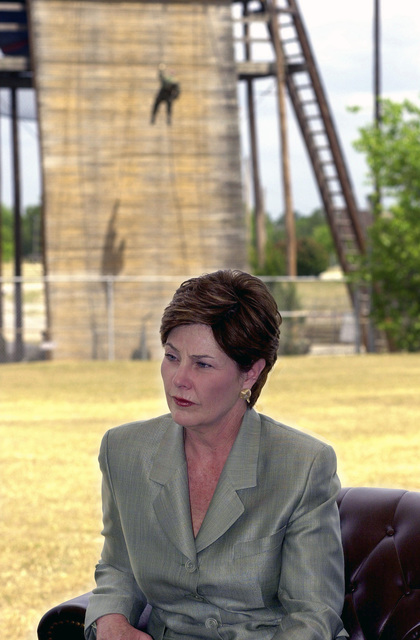 "In the background, Army trainees descend the rappelling wall as First Lady Laura Bush gives an interview to the local media, at Fort Jackson, South Carolina. Mrs. Bush, a former teacher, visited the post in observance of National Teachers Day to promote the ""Troops to Teachers"" program, where retired service members transition from active duty to teachers. Mrs. Bush said retired service members make great role models and some of the best teachers because of the training they receive during their time in the military"