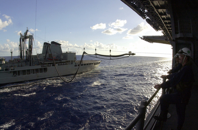 Fuel hoses from the Australian ship HMAS Success (OR 304), an Auxiliary Oiler Replenishment (AOR) vessel, extend towards the USS Essex (LHD 2), as it is replenished at sea off the coast of Queensland, Australia, as part of support for Exercise TANDEM THRUST 01. TANDEM THRUST 2001 a combined US, Australian, and Canadian military exercise for crisis action planning and execution of contingency response operations. The biannual exercise is held in the vicinity of Shoalwater Bay training area in Queensland, Australia