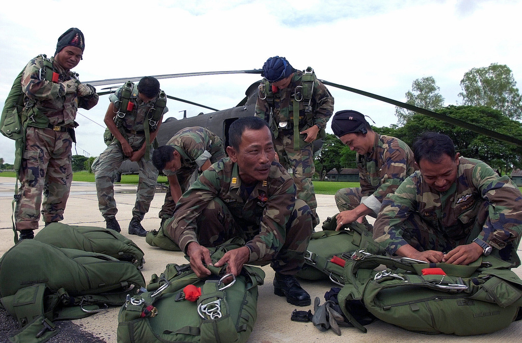 Members from the Royal Thailand Armed Forces prepare their parachutes prior to boarding an Army CH-47 Chinook helicopter at Phitsanulok, Thailand. The U.S. and Thai airborne soldiers are participating in a combined Army High Altitude Low Opening (HALO) jump in preparation for the opening ceremony activities at this year's Exercise COBRA GOLD. COBRA GOLD is regularly scheduled, joint-combined exercise designed to ensure regional peace and strengthen the ability of the Royal Thai Armed Forces to defend Thailand or respond to regional contingencies. This year's exercise, the 20th in the series, will focus on peace enforcement operations