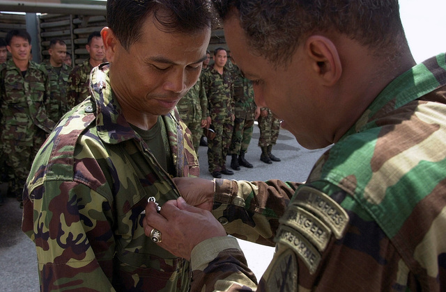 Army Command Sergeant Major Hoopy Qualls, 1ST Special Forces Group, Fort Lewis, Washington, presents Army parachutist wings to members of the Thai Armed Forces after participating in a joint-combined High Altitude Low Opening (HALO) jump at Phitsonulok, Thailand, at this year's Exercise COBRA GOLD O1. COBRA GOLD is regularly scheduled, joint-combined exercise designed to ensure regional peace and strengthen the ability of the Royal Thai Armed Forces to defend Thailand or respond to regional contingencies. This year's exercise, the 20th in the series, will focus on peace enforcement operations