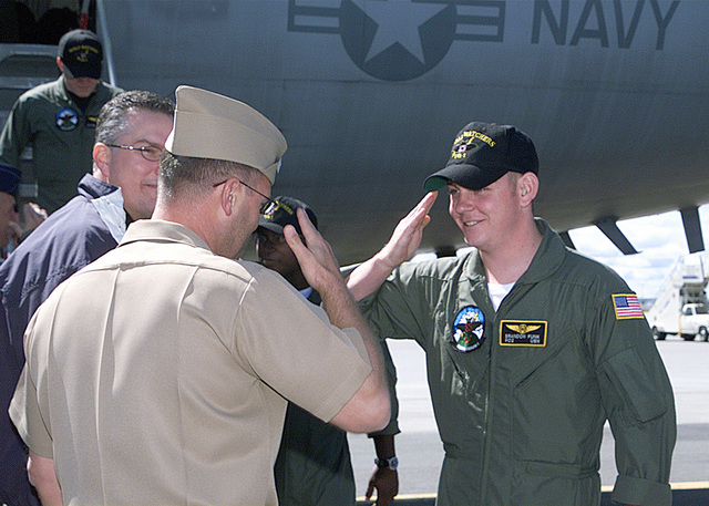 Navy Lieutenant Gary Hoyt, (right), physician, returns a salute to PETTY Officer 2nd Class Brandon J. Funk, member of the EP-3E Aries II aircrew. The crew arrived at Fairchild Air Force Base, Washington, for continued debriefing with the Joint Personnel Recovery Agency, after being detained in China due to an aircraft incident. The Joint Personnel Recovery Agency (JPRA) functions as the Department of Defense Office of Primary Responsibility for DoD-wide personnel recovery matters