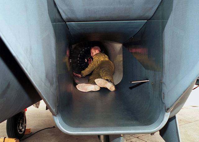 US Air Force STAFF Sergeant Dave Williams from the 494th Fighter Squadron, 48th Fighter Wing, Royal Air Force Lakenheath, England, inspects an F-15 Eagle aircraft intake to verify there are no cracks, loose rivets or damage to the engine after flight
