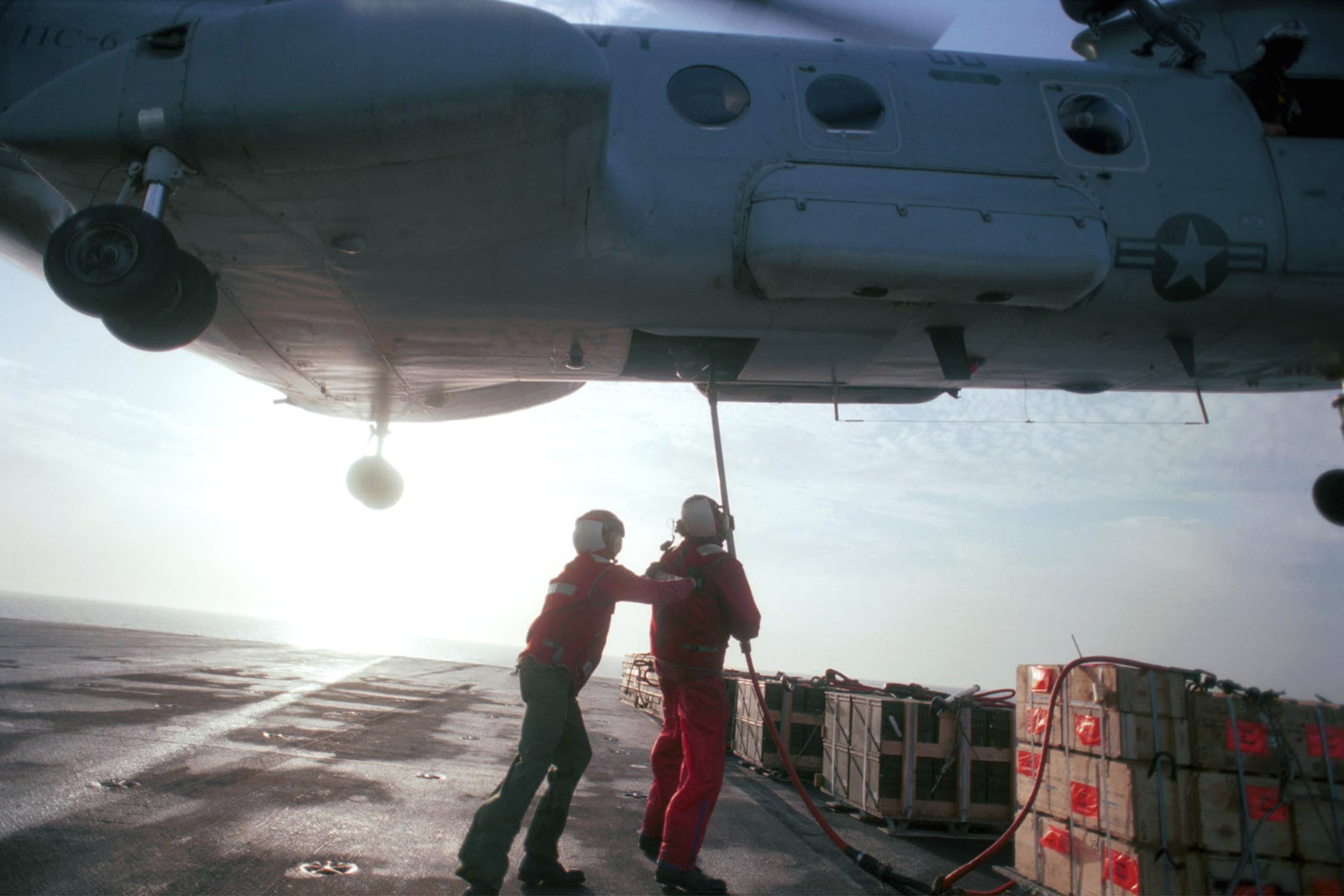 US Navy Aviation Ordnanceman Second Class Toby Snowden and US Navy AIRMAN Terrence Hill hook ordnance containers to an CH-46D Sea Knight to be delivered to USS ENTERPRISE (CVN 65) (not shown) during a weapons offload on the flight deck of USS HARRY S. TRUMAN (CVN 75)