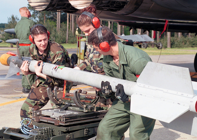 Close up of SENIOR AIRMAN (SRA), Dave Anelundi, AIRMAN First Class (A1C), Crystal Getz and STAFF Sergeant (SSGT), Clint Holman, USAF, 494th Fighter Squadron, 48th Fighter Wing (FW), Royal Air Force (RAF), Lakenheath, UK as they place a AIM-9 Sidewinder Missile on a MJ-1 weapons loader, after removing it from a USAF F-15 Eagle aircraft from the 48TH FW. In the background SSGT Scott Spraberry performs a routine post flight inspection of the aircraft